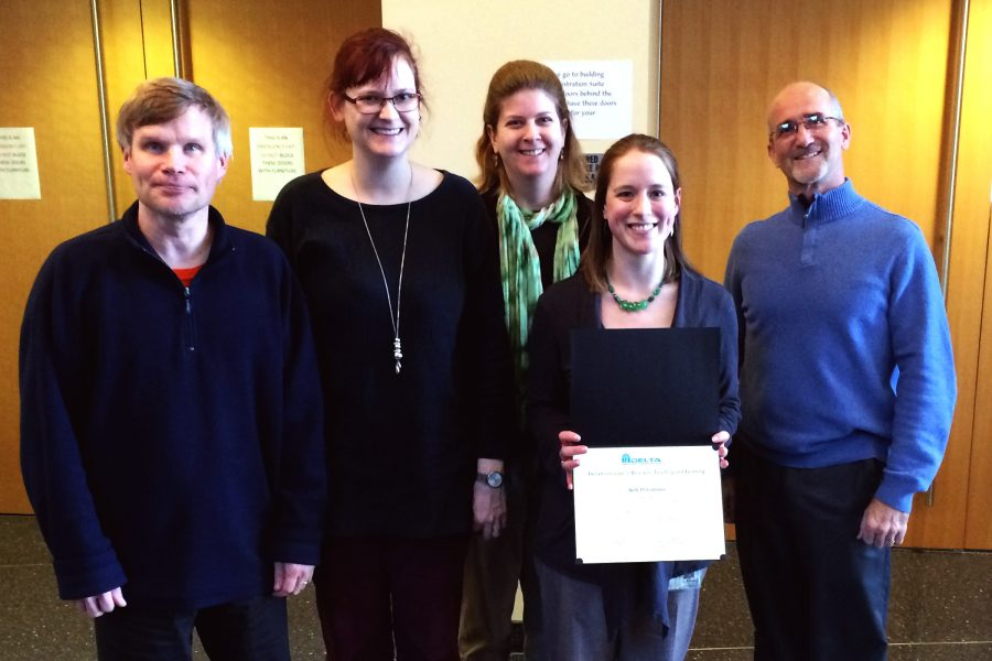 Five people are posed close together in a line facing the camera, all smiling. One person holds a certificate in front of her, displaying it to the camera.