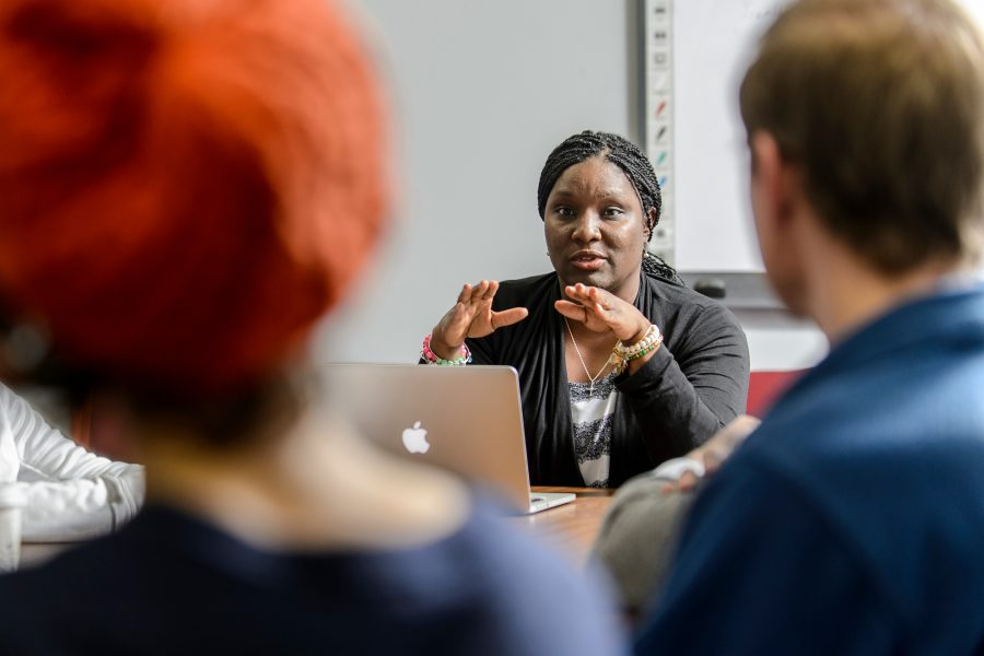 People are seated around a table, with the focal person framed by two out-of-focus heads. This person is speaking, with hands raised in a gesture in front of her chest. Link goes to page of what we offer.