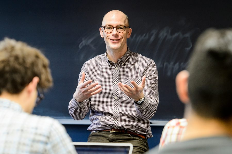 A male instructor wearing glasses and a collared shirt faces the camera, framed by the backs of students' heads. His hands are raised mid-gesture as he speaks, with a blackboard in the background.